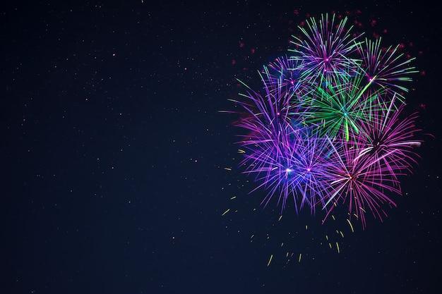 Niesamowite fajerwerki niebieski fioletowy zielony celebracja znajduje się po prawej stronie nad nocnym niebem, kopia przestrzeń. dzień niepodległości, 4 lipca, pozdrawiam tło wakacje nowy rok.