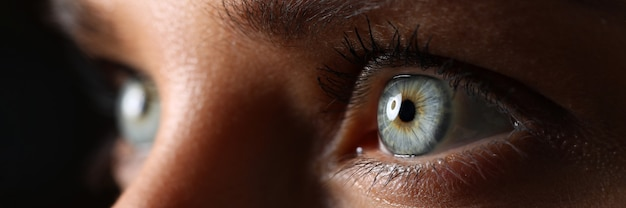Niesamowite kobiece zielone i niebieskie oczy w zbliżeniu techniki słabego światła