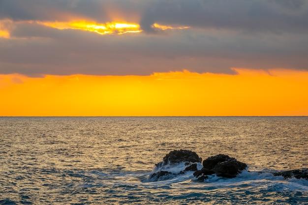Niesamowite kolory zachodu słońca na zachmurzonym niebie. kamienie przybrzeżne w spokojnym morzu