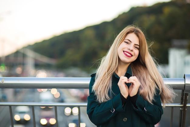 Niesamowite ładna kobieta pokazując znak serca z jej palców. miejsce na tekst