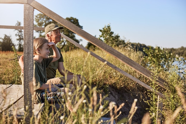 Niesamowite miejsce do wędkowania, dwóch mężczyzn szykujących się do łowienia ryb z jeziora, ojciec i syn siedzący przy drewnianym stojaku nad rzeką, blondyn spoglądający w dal z ręką przy czole.