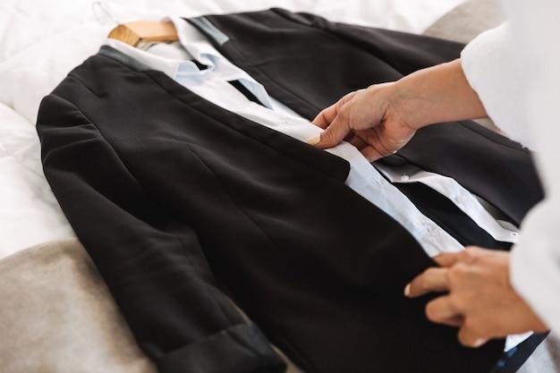 Niesamowite młody biznes kobieta trzyma ubrania wizytowe w pomieszczeniu w domu.