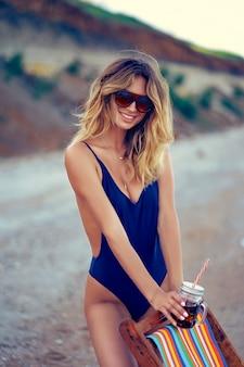 Niesamowite piękno blond kobieta w okularach przeciwsłonecznych, strój kąpielowy relaks na plaży i pije koktajl. koncepcja wakacji letnich