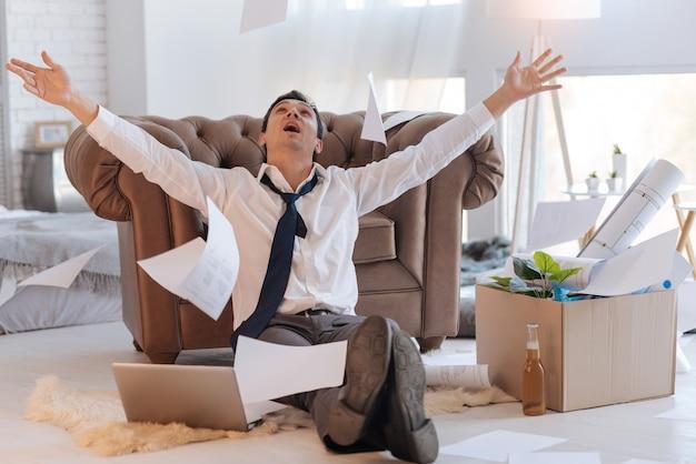 Niesamowite. podekscytowany, emocjonalny młody mężczyzna siedzi na podłodze z laptopem u boku i wyrzuca dokumenty w powietrze i patrzy, jak spadają