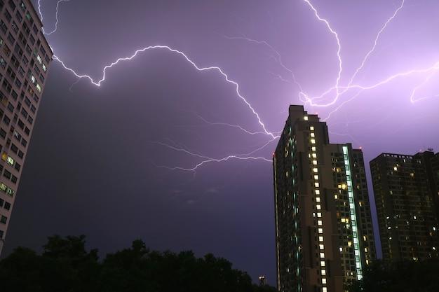 Niesamowite prawdziwe uderzenia pioruna na miejskim nocnym niebie