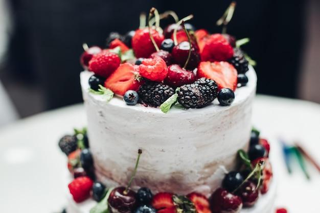 Niesamowite, świeże apetyczne słodkie ciasto z kremem pokrytym orzeźwiającymi owocami i jagodami