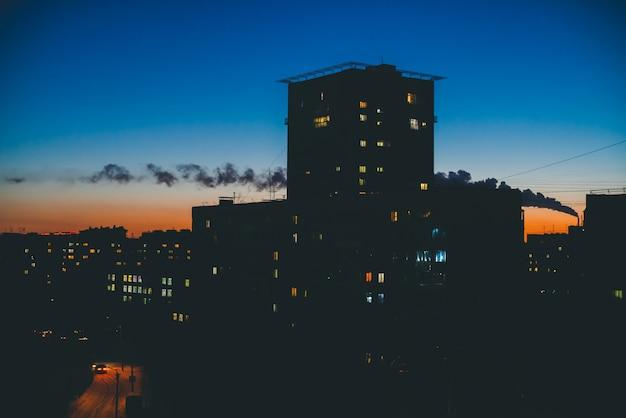 Niesamowite sylwetki budynków ze świetlistymi oknami na tle ciepłego nieba słońca.
