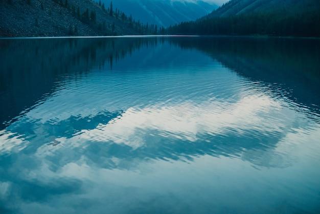Niesamowite sylwetki gór i niskie chmury odbijające się w górskim jeziorze.