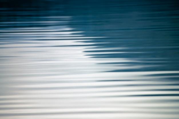 Niesamowite teksturowane tło spokojnej powierzchni niebieski czystej wody.