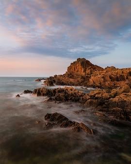 Niesamowite ujęcie kamienistej plaży w pobliżu fort houmeton na tle zachodu słońca na guernsey