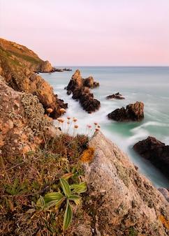 Niesamowite ujęcie kamienistej plaży w zatoce jaonnet podczas zachodu słońca