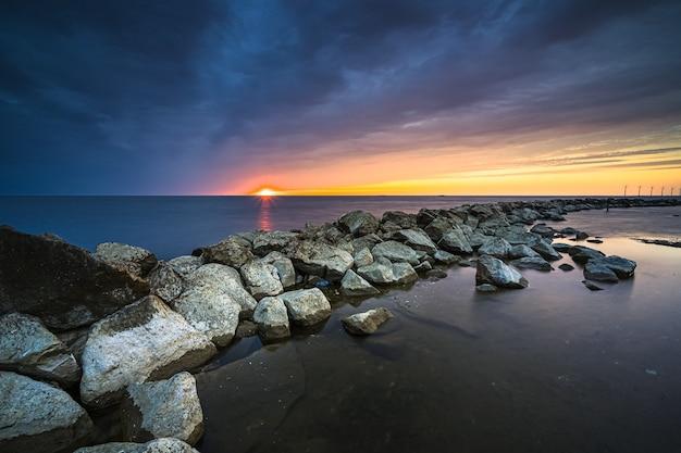 Niesamowite ujęcie naturalnej skalistej granicy na pięknym zachodzie słońca