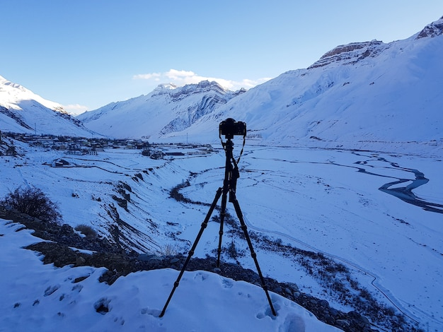 Niesamowite ujęcie pasma górskiego pokrytego śniegiem na pierwszym planie stojaka na aparat