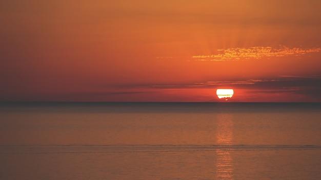 Niesamowite ujęcie pięknego krajobrazu morskiego na pomarańczowym zachodzie słońca