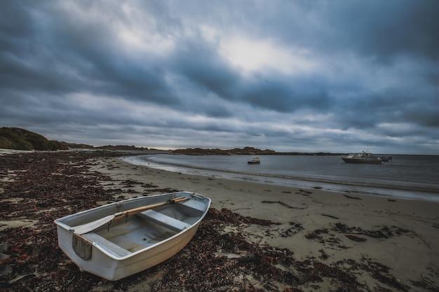Niesamowite ujęcie starej łodzi na piaszczystej plaży ze spokojnym oceanem i innymi łodziami pod zachmurzonym niebem