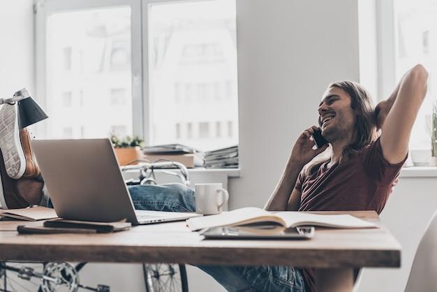 Niesamowite wieści! przystojny młody mężczyzna z długimi włosami rozmawia przez telefon komórkowy i wygląda na szczęśliwego siedząc w swoim miejscu pracy w biurze