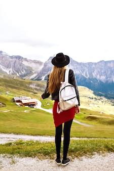 Niesamowite wrażenia z podróży obraz pięknej stylowej kobiety pozującej do tyłu i patrzącej na zapierający dech w piersiach widok na góry