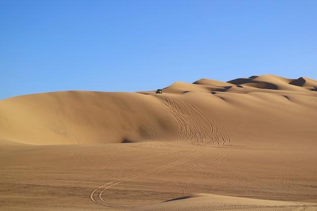 Niesamowite wydmy z falami piasku i odciskami kół z wydmowych buggy, pustynia huacachina, peru
