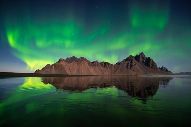 Niesamowite zorza polarna, aurora borealis tańczy na górze vesturhorn w islandii