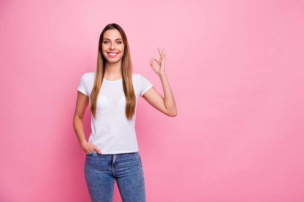 Niesamowitej atrakcyjnej pani pokazującej ręce symboli okey wyrażających zgodę toothy uroczy uśmiechnięty nosić na co dzień biały t-shirt jeansy