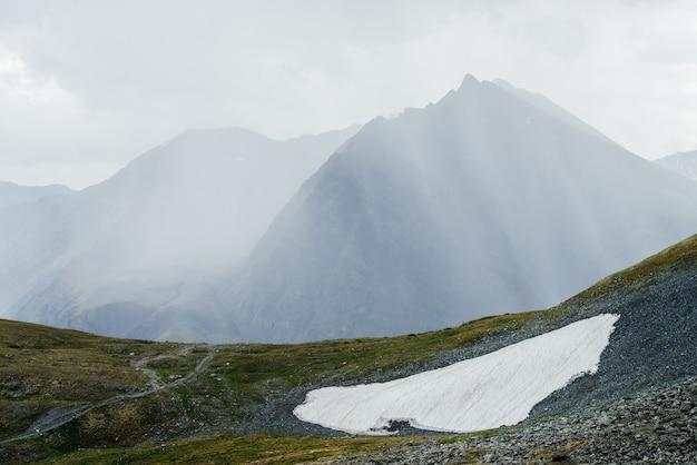 Niesamowity alpejski widok na ogromną górę z ostrym szczytem w promieniach słońca przez chmury. cudowna góralska sceneria z wielką spiczastą skałą za śniegiem na przełęczy w słońcu w pochmurny dzień.
