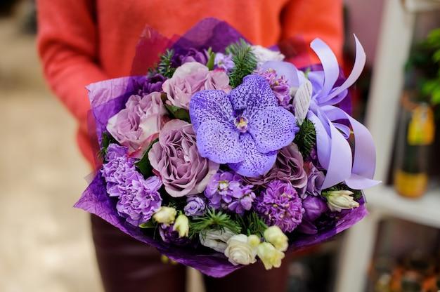 Niesamowity fioletowy zimowy bukiet kwiatów w rękach kobiety