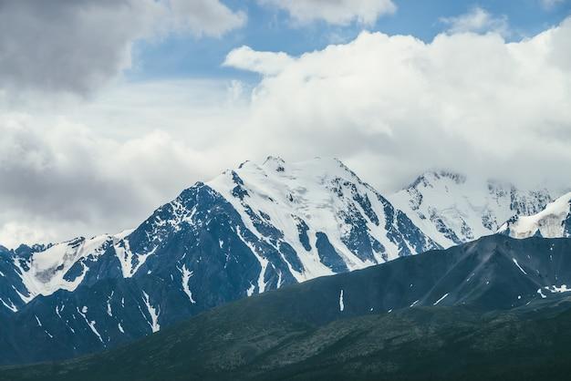 Niesamowity krajobraz gór z wysokim ośnieżonym pasmem górskim wśród białych chmur w błękitne niebo. nastrojowa sceneria górska ze śnieżnobiałym dużym grzbietem górskim w pochmurną pogodę. cudowny śnieżny szczyt