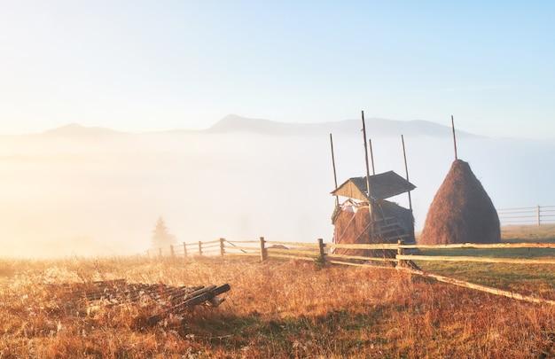 Niesamowity krajobraz górski z mgłą i stogiem siana jesienią.