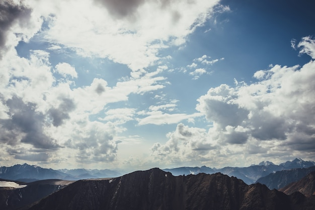 Niesamowity krajobraz górski z sylwetką skalistej góry pod błękitnym pochmurnym niebem w słońcu. klimatyczny krajobraz alpejski z sylwetkami gór i chmurami w słonecznym niebie. ostry szczyt górski.