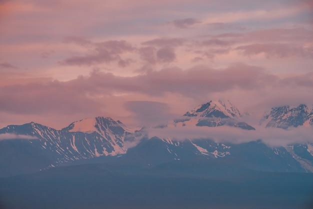 Niesamowity krajobraz górski z wielkim ośnieżonym pasmem górskim oświetlonym pomarańczowym słońcem świtu wśród niskich chmur. minimalna sceneria alpejska z zaśnieżonym grzbietem wysokich gór pod zachmurzonym niebem o zachodzie słońca lub o wschodzie słońca.