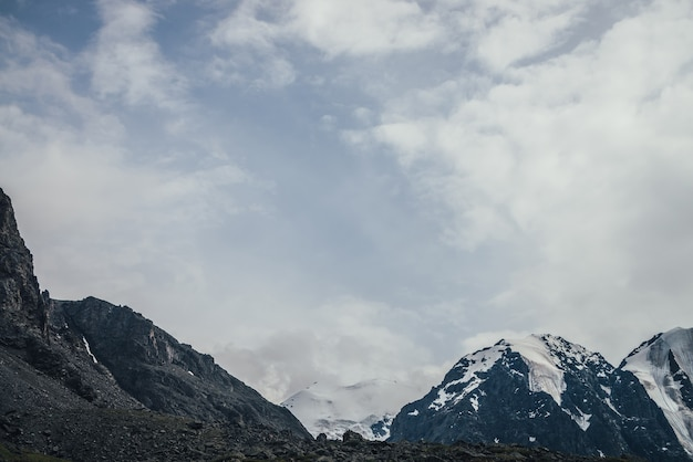 Niesamowity krajobraz górski z wielkim ośnieżonym szczytem w zachmurzonym niebie. klimatyczna pochmurna sceneria z wysoką górą z lodowcem. duże góry ze śniegiem w niskich chmurach. piękne ośnieżone góry.