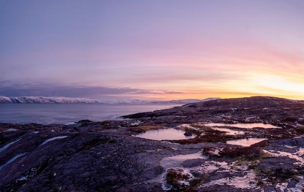 Niesamowity krajobraz polarny o wschodzie słońca z białą, śnieżną granią góry