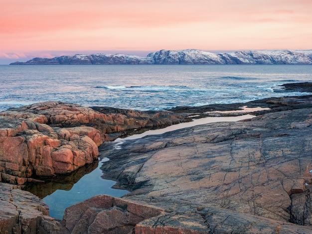 Niesamowity krajobraz wschodu słońca z polarnym białym śnieżnym pasmem gór. cudowny górski krajobraz z wąwozem i przylądkiem na brzegu morza barentsa. teriberka