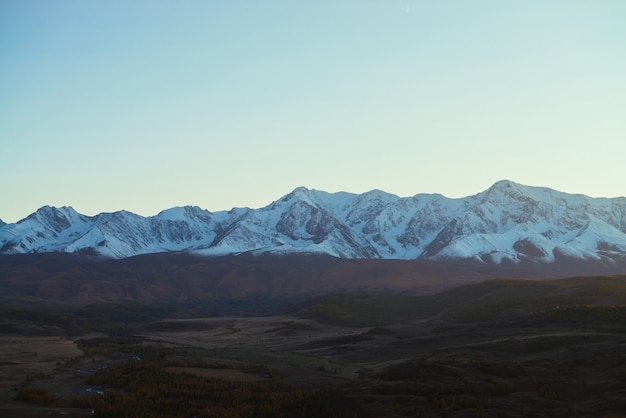Niesamowity krajobraz z górską doliną ze wzgórzami i lasem w jesiennych kolorach w cieniu z widokiem na wielkie ośnieżone pasmo górskie o zachodzie słońca. wysokie pokryte śniegiem góry i jesienna dolina przy słabym oświetleniu