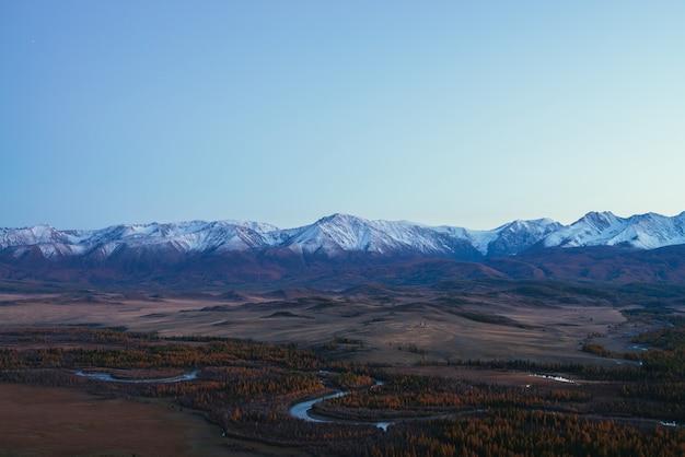 Niesamowity krajobraz z górską serpentynami rzecznymi w dolinie wśród wzgórz i lasów w jesiennych kolorach z widokiem na wielkie ośnieżone pasmo górskie o zachodzie słońca. wysokie, pokryte śniegiem góry i jesienna dolina.