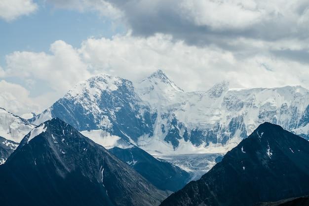 Niesamowity krajobraz z pięknymi ogromnymi lodowcowymi górami w pochmurną pogodę.