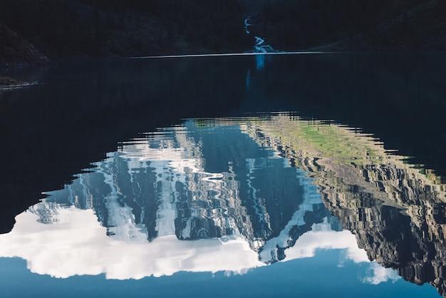 Niesamowity lodowiec pod niebieskim niebem. grań ze śniegiem odzwierciedlenie na górskie jezioro. ogromna chmura na gigantycznych wspaniałych zaśnieżonych górach. klimatyczny nastrojowy krajobraz majestatycznej przyrody wyżyn w matowych odcieniach.