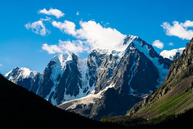 Niesamowity lodowiec pod niebieskim niebem. ogromna chmura na gigantycznych cudownych śnieżnych górach w świetle słonecznym. bogata roślinność i las wyżynny. klimatyczny, minimalistyczny krajobraz majestatycznej przyrody w słoneczny dzień.