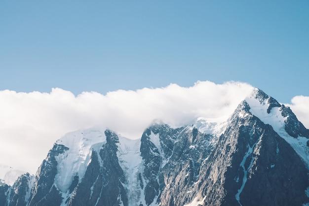 Niesamowity lodowiec pod niebieskim niebem. pasmo górskie ze śniegiem. ogromna chmura na gigantycznych wspaniałych zaśnieżonych górach. klimatyczny, minimalistyczny nastrojowy krajobraz majestatycznej przyrody wyżyn w matowych odcieniach.
