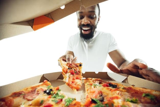 Niesamowity mężczyzna afro-amerykański przygotowuje niewiarygodne jedzenie z akcją, szczegółami i jasnymi emocjami, profesjonalny kucharz na białym tle na tle białego studia. nowoczesna kuchnia, grafika. zbliżenie, szeroki kąt.