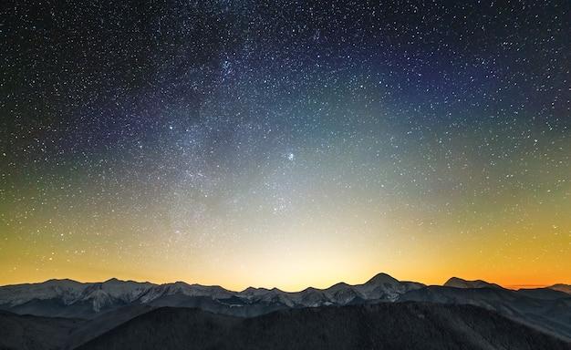 Niesamowity nocny krajobraz górski z wysokimi szczytami i jasnym gwiaździstym niebem powyżej.