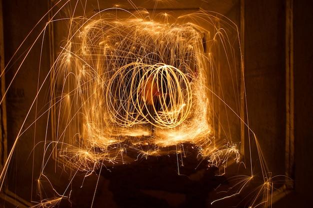 Niesamowity ogień z wełny stalowej krąży w nocy ze świecącymi iskrami