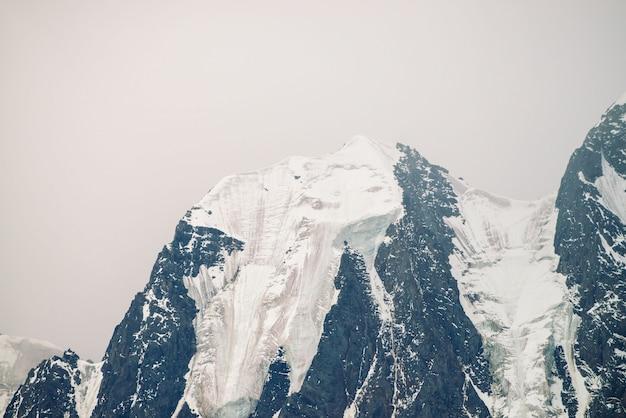 Niesamowity ogromny lodowiec. śnieżny pasmo górskie w chmurzącym niebie. cudowna gigantyczna skalista grań ze śniegiem we mgle. klimatyczny, minimalistyczny krajobraz majestatycznej przyrody wyżyn. spokojny górski krajobraz.