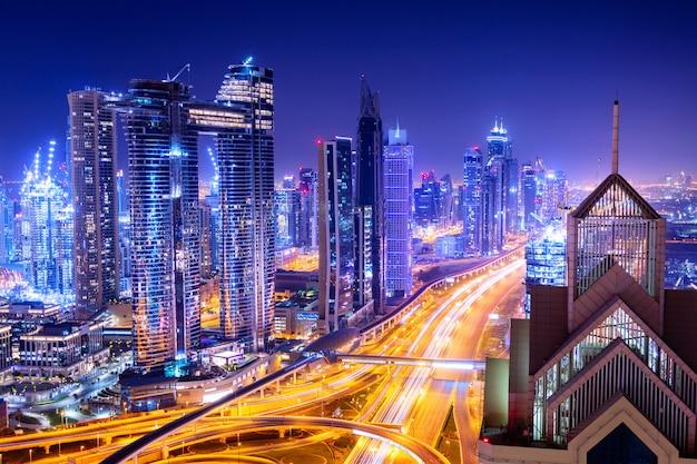 Niesamowity pejzaż z oświetlonymi drapaczami chmur. śródmieście dubaju w nocy, zjednoczone emiraty arabskie.