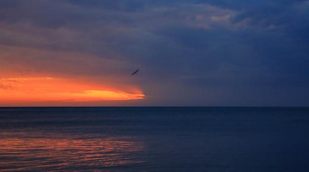 Niesamowity piękny zachód słońca. słońce wchodzi w morze i barwi niebo jasnym pomarańczowym kolorem.