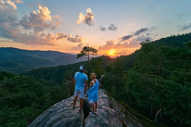 Niesamowity pomarańczowy wschód słońca zza chmur w górach. kilku turystów na szczycie góry. sosnowy las w górach. krajobraz górski. podróże, wakacje, turystyka.