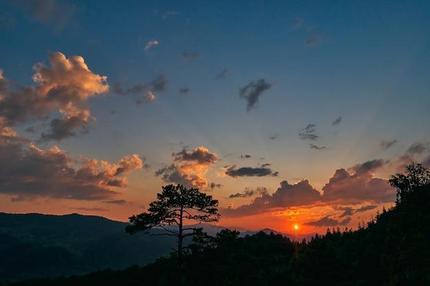 Niesamowity pomarańczowy wschód słońca zza chmur w górach. wielobarwne niebo przed promieniami słońca. sosna na górze w cieniu słońca. podróże, wakacje, turystyka.