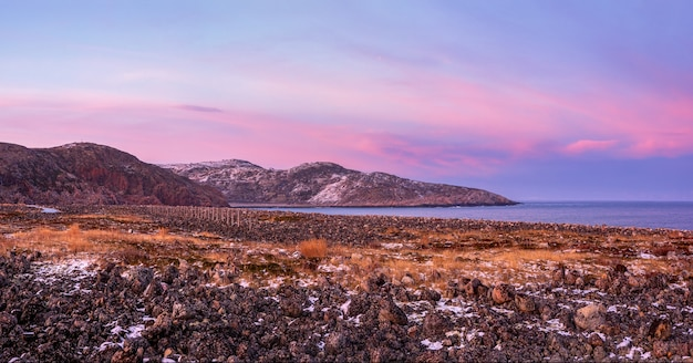 Niesamowity różowy wschód słońca polarny krajobraz z górami.