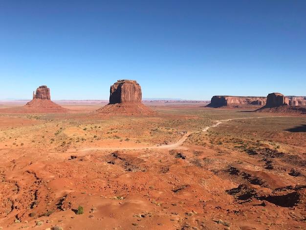 Niesamowity widok monument valley z czerwoną pustynią, błękitne niebo i chmury rano. monument valley w arizonie z west mitten butte, east mitten butte i merrick butte.