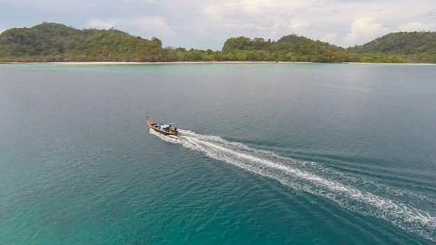 Niesamowity widok na łódź pływającą na otwartym morzu w wietrzny dzień. widok drani - kąt oka ptaków. - zwiększenie przetwarzania koloru.